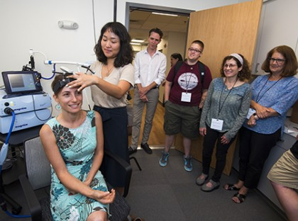 Brain researcher Marina Bedny (seated), with assistance from doctoral student Judy Sein Kim, conducts a demonstration.  IMAGE CREDIT: LARRY CANNER / HOMEWOOD PHOTOGRAPHY